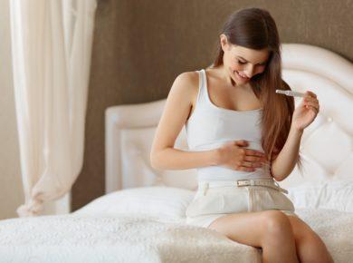 Glückliche Frau mit Schwangerschaftstest