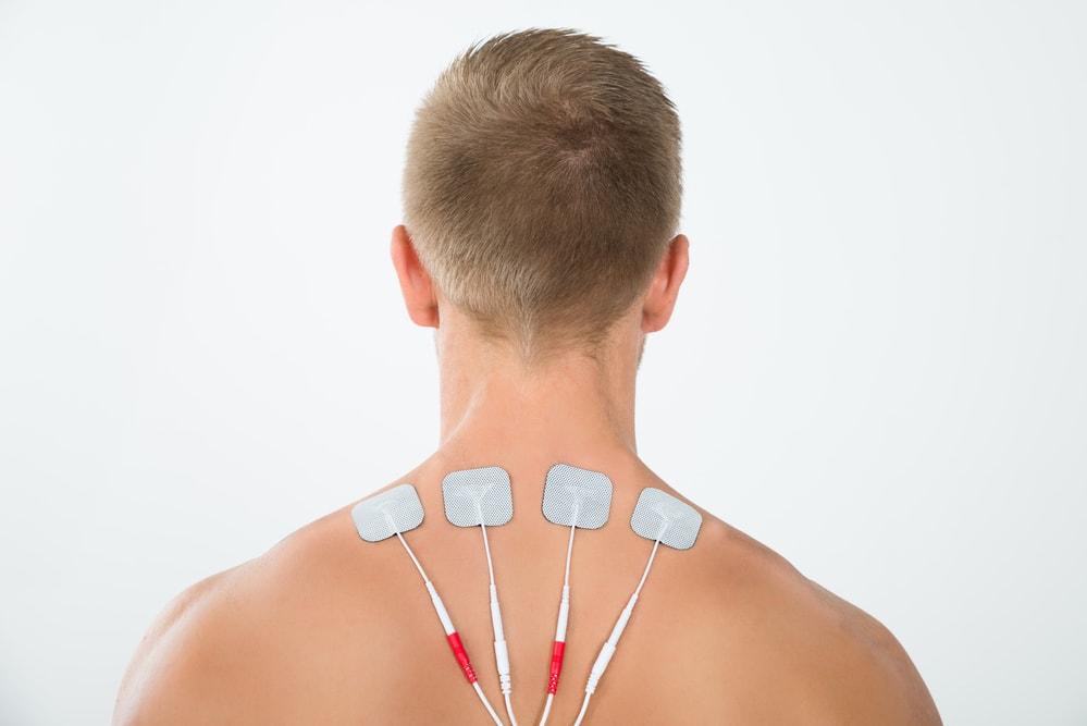 Mann mit Tens Elektroden am Nacken