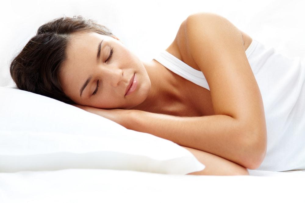 Frau schläft auf Kirschkernkissen